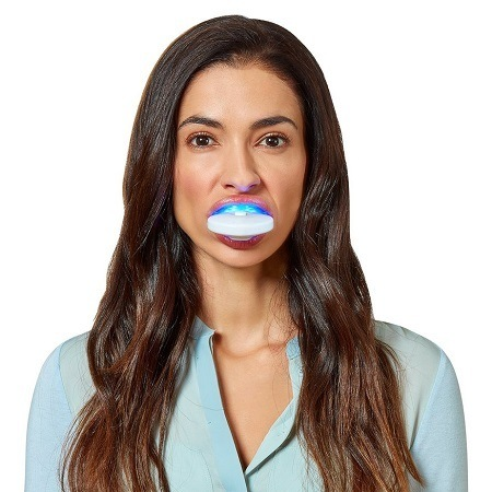 Woman Holding Whitening Kit In Mouth